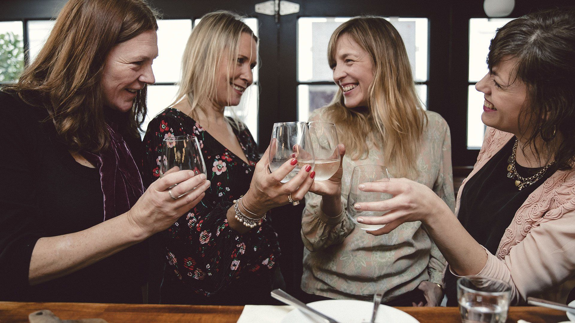 4 females toasting in a restaurant